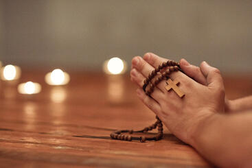 Hands with Rosary and Candles on Table